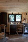 Minimalistische Küchenzeile vor Fenster in holzverkleideter Küche mit Tierfellteppich