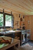 Minimalistische Küchenzeile vor Fenster in holzverkleideter Waldhausküche