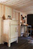 Rustikaler Holzschrank in moderner, holzverkleideter Küche mit ländlichem Flair