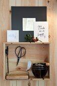 Bürste und Schere neben Schalenstapel in kleinem Holzkistchen mit Grusskarten an Holzwand befestigt