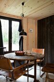 Freischwinger mit hellbraunem Lederbezug um rundem Holztisch in Hüttenambiente