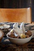Weisses Porzellan-Eichhörnchen zwischen Walnüssen und Pralinen in Schale