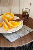 Orangenschnitzen auf weißem Telle und Teeglas auf rundem Beistelltisch