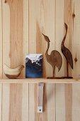 Vogelfiguren aus Holz auf Konsolenregalbrett vor Kiefernholzwand arrangiert
