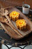 Honigfarbene Teelichter auf Holzschale mit Salatbesteck