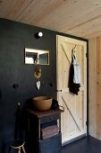 Vintage Metallschränkchen mit Holz-Waschschüssel vor schwarzer Wand neben naturbelassener Holztür, Messingtierfigur als Wasserhahn