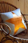 Kissen mit goldenem Sternenmotiv auf Rattanstuhl