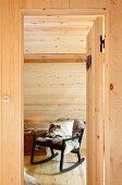 Blick durch offene Zimmertür auf gemütlichen schwarzen Schaukelstuhl mit Tierfell und Kissen unter Dachschräge