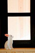 weiße Hasenfigur auf Holzfenstersims vor schwarzem Fensterrahmen