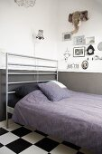Bed with modern headboard made from metal bars; pictures and fabric hunting trophy on wall