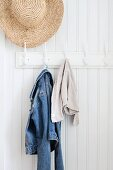 Straw hat and denim jacket hanging from coat pegs on white wood panelling