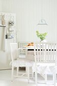 Scandinavian, white dining set with frilled cushions and tiered baskets suspended from peg on door in background