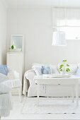 White seating area with country-house sofa, wicker chairs and shabby-chic lamp above coffee table