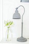 Grey-painted, vintage lamp and white irises in milk bottle on side table