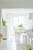 White dining area with vintage chest of drawers