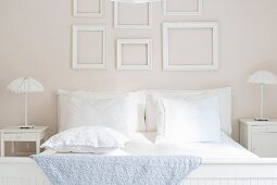 Double bed with white bed linen flanked by ruched lamps on bedside tables below collection of empty picture frames on wall