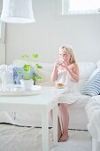 Blonde girl drinking milk on white sofa
