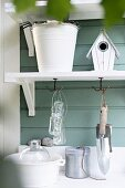 Gardening utensils on bracket shelves on green wooden wall of garden shed