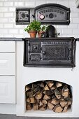 Black, cast iron oven integrated in masonry kitchen counter with firewood stored in niche below