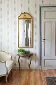 Framed mirror above console table with curved legs against wall with white and blue wallpaper