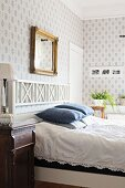 Double bed with white wooden headboard in rustic bedroom with white and blue patterned wallpaper
