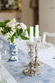 Silver candlesticks and posy on white and blue patterned tablecloth