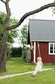Little girl playing on swing hung from tree in front of wooden house in summery garden