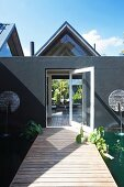 Wooden bridge over pond leading to grey-painted extension with open door