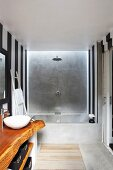 Designer bathroom; washstand with rustic wooden counter, black and white, vertically striped walls and concrete bathtub