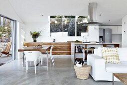 Designer kitchen with dining area in open-plan interior; white couch in foreground