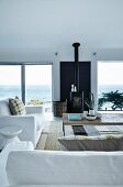 White sofa set around delicate coffee table, wood-burning stove flanked by French windows in contemporary living room with panoramic view of ocean