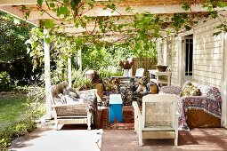 Comfortably furnished terrace below climber-covered pergola adjoining rustic wooden house