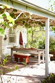 View from garden to sunny terrace with climber-covered pergola, rustic bench and white table outside white wooden house