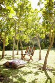Floor cushions and simple, wooden deckchair with striped cover in summer garden