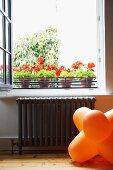 Orange 70s floor lamp below open window and potted red geraniums on windowsill