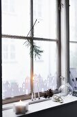 Paper city skyline stuck to window, candles and pine cones on windowsill