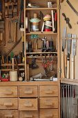 Hand tools in traditional tool cabinet in carpenter's workshop