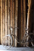 Vintage bicycle in front of stock of wooden beams in barn of rough-wood carpenter's workshop