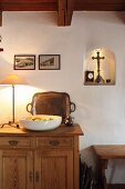 White fruit bowl and table lamp on wooden sideboard against wall next to shrine in small, illuminated niche