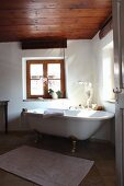 Free-standing bathtub below window in renovated bathroom