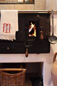 Wood-fired cooker with cloth and ladle hung from towel rail and view of fire through open firebox door