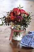 Posy of roses and daisies in glass jar decorated with gingham ribbon