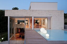 Spherical lamps in pool outside contemporary house