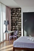 Designer lamp on small table and plastic chair in front of floor-length window curtains next to wallpaper mural with bookcase motif