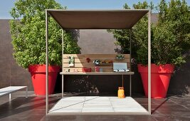 Terrace with cubic pergola flanked by trees in red, oversized plant pots in courtyard