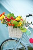 Summer bouquet in white basket hung on bicycle handlebars