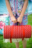 Rolled, red picnic blanket being held by girl in garden