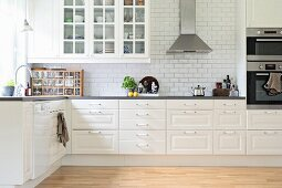 Kitchen counter with white base units and wall units with lattice doors
