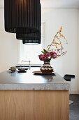 Blumenstrauss in Silbervase auf freistehender Küchentheke mit Steinplatte, darüber Pendelleuchten mit schwarzem Stoffschirm