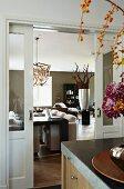 Teilweise sichtbarer Blumenstrauss auf Theke, gegenüber offene Schiebetür und Blick in modernen Wohnraum